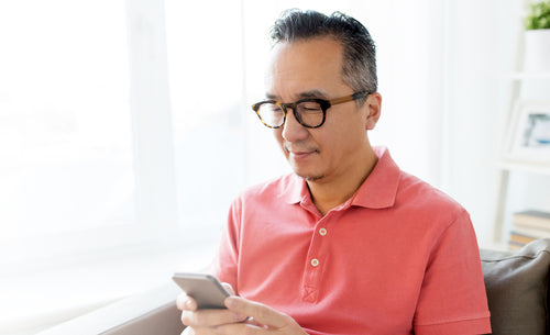 Older Asian man with glasses and type 2 diabetes uses smartphone to access One Drop glucose predictions