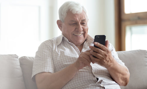 Older man with white hair uses smartphone to access One Drop's Digital Membership and virtual health coach