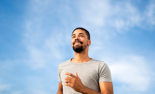 Young man in gray t-shirt runs outside against a blue sky