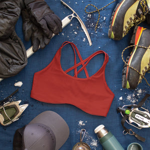 Top down view of High Cut Têra Kaia TOURA Basewear Top in color Mars Red surrounded by various ice climbing gear including crampons, mountaineering boots, an ice axe, thermos, and snow gloves. Photo illustrates how to style the TOURA Top for outdoor adventure.