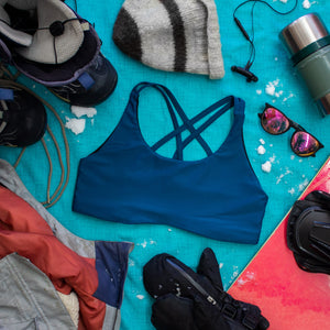 Top down view of High Cut Têra Kaia TOURA Basewear Top in color Neptune Blue surrounded by various snowboarding gear including a jacket, beanie, snow gloves, sunglasses, and snow board. Photo illustrates how to style the TOURA Top for outdoor adventure.
