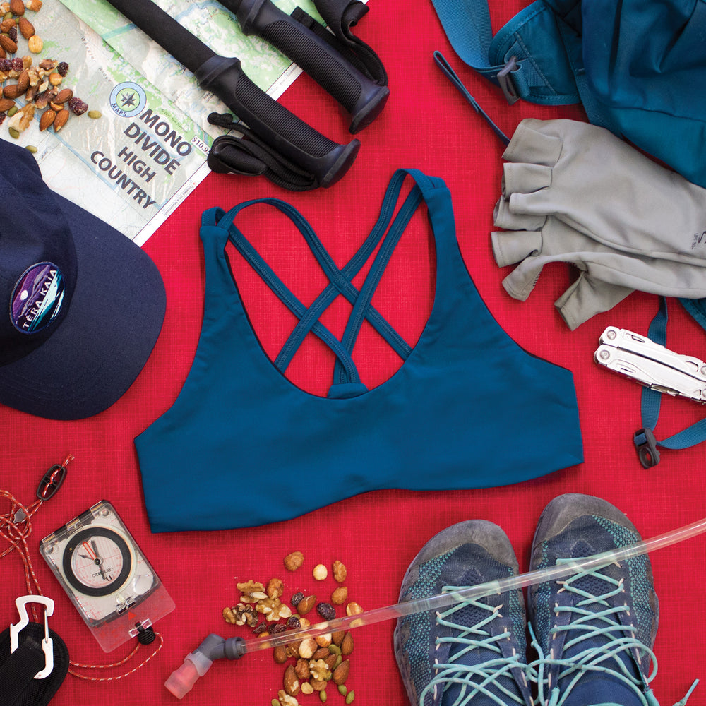 Top down view of Low Cut Têra Kaia TOURA Basewear Top in color Neptune Blue surrounded by various hiking gear including a map, hiking poles, hiking gloves, compass, trail mix, and approach shoes. Photo illustrates how to style the TOURA Top for outdoor adventure.