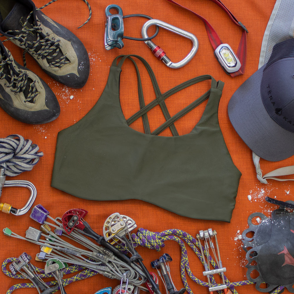 Top down view of High Cut Têra Kaia TOURA Basewear Top in color Olive Green surrounded by various trad climbing gear including cams, nuts, cordalette, climbing shoes, belay anchor, atc belay device, crack climbing gloves, and a headlamp. Photo illustrates how to style the TOURA Top for outdoor adventure.