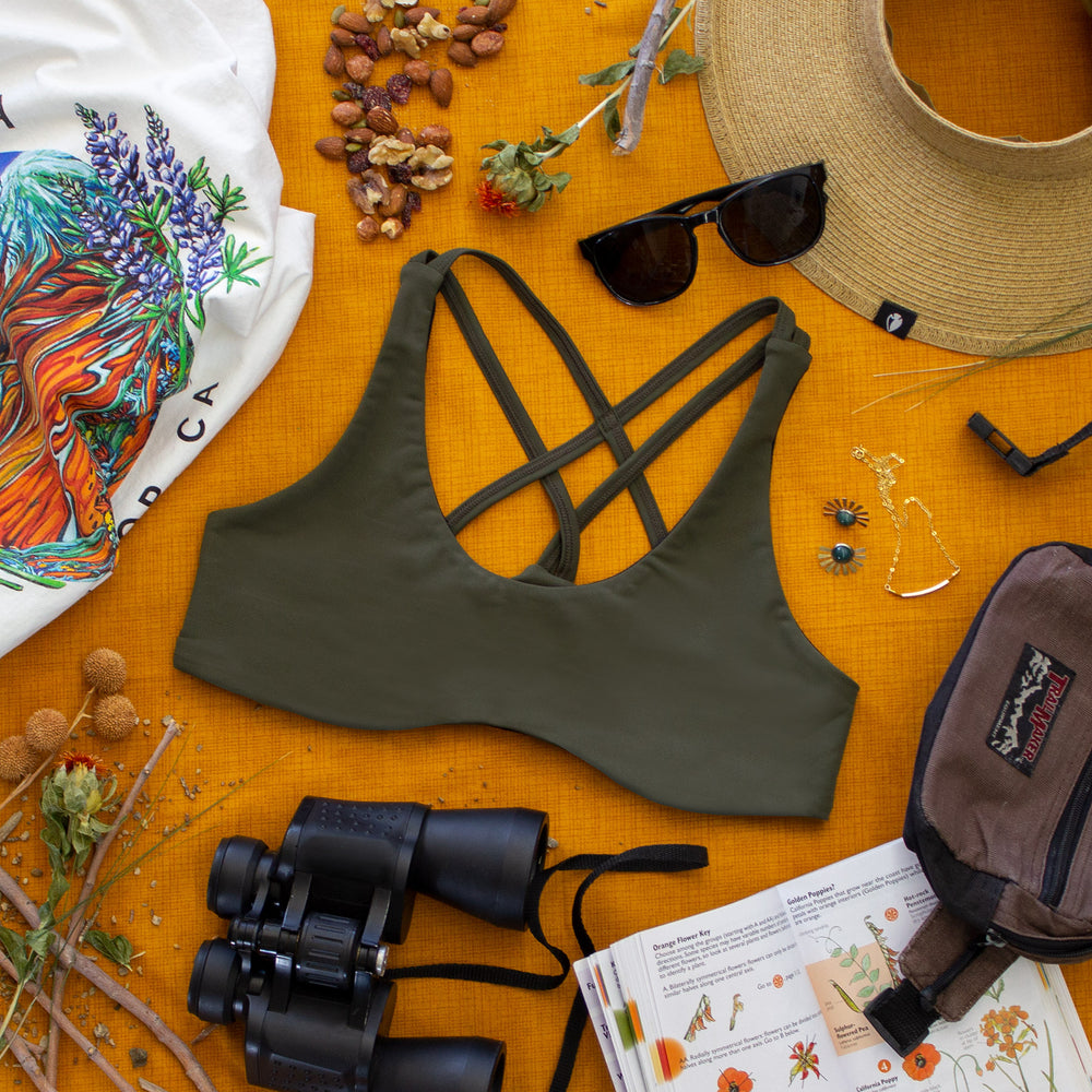 Top down view of Low Cut Têra Kaia TOURA Basewear Top in color Olive Green surrounded by various hiking and nature walk gear including a sun hat, binoculars, plant identification book, sun hat, and sun glasses. Photo illustrates how to style the TOURA Top for outdoor adventure.