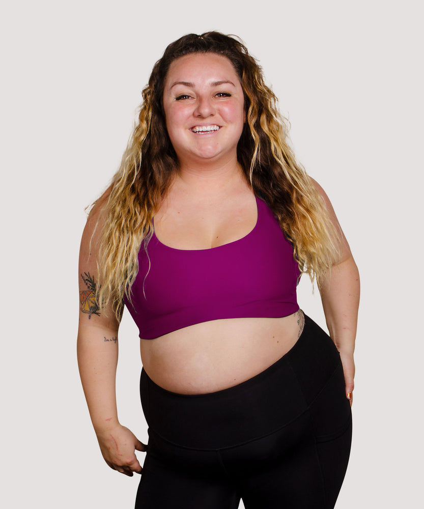 Model Tess is wearing the High Cut Têra Kaia TOURA Basewear Top in Size 8 Color Orchid Purple. Basewear is a comfortable sports bra for outdoor activity including hiking, climbing, and swimming. Model Tess is a full figured and curvy white woman with a large cup size.