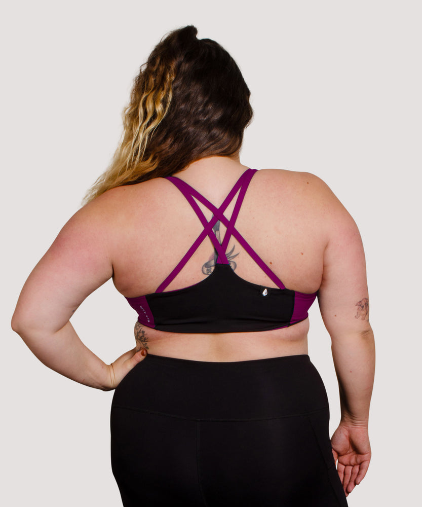Model Tess is wearing the High Cut Têra Kaia TOURA Basewear Top in Size 8 Color Orchid Purple. Basewear is a comfortable sports bra for outdoor activity including hiking, climbing, and swimming. The strappy criss-cross racer back design is a defining feature of the TOURA. Model Tess is a full figured and curvy white woman with a large cup size.