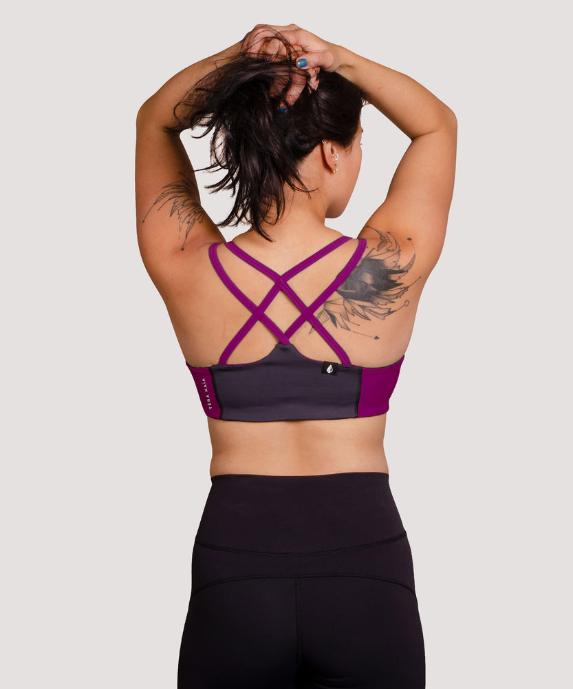 Model Jess stretches in the High Cut Têra Kaia TOURA Basewear Top in Size 6 Color Orchid Purple. Basewear is a comfortable sports bra for outdoor activity including hiking, climbing, and swimming. The strappy criss-cross racer back design is a defining feature of the TOURA. Model Jess is an asian woman of medium athletic build. She has a medium cup size and can wear both the High Cut and the Low Cut.