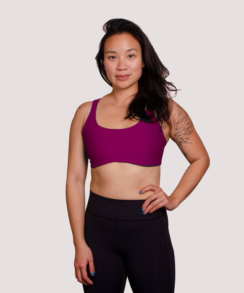 Model Jess is wearing the High Cut Têra Kaia TOURA Basewear Top in Size 6 Color Orchid Purple. Basewear is a comfortable sports bra for outdoor activity including hiking, climbing, and swimming. Model Jess is an asian woman of medium athletic build. She has a medium cup size and can wear both the High Cut and the Low Cut.