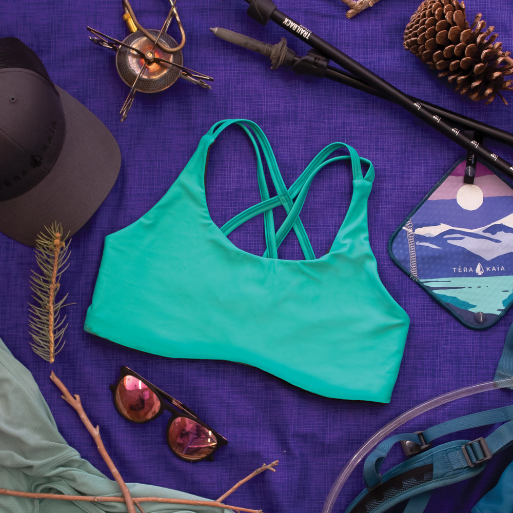 Top down view of High Cut Têra Kaia TOURA Basewear Top in color River Blue surrounded by various backpacking gear including a portable stove, camel back, kula pee cloth, sun hoodie, and hiking poles. Photo illustrates how to style the TOURA Top for outdoor adventure.