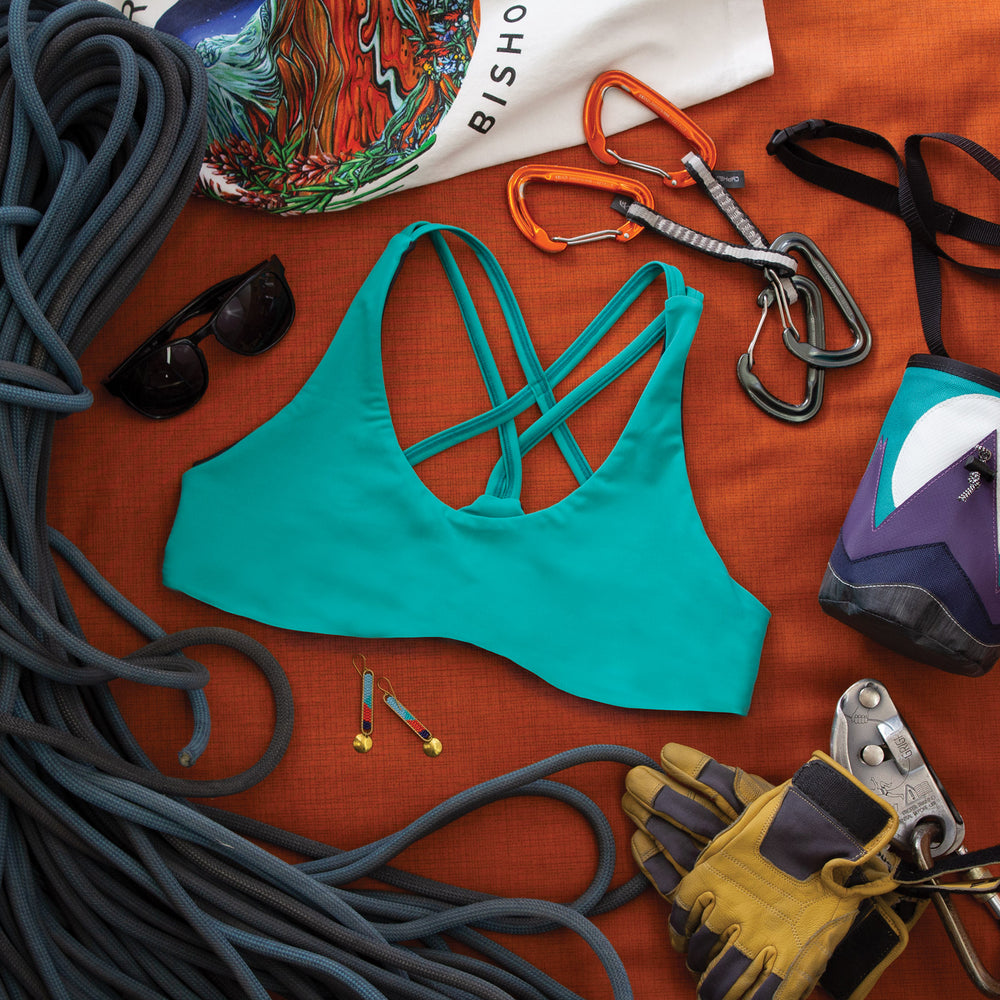 Top down view of Low Cut Têra Kaia TOURA Basewear Top in color River Blue surrounded by various climbing gear including a chalk bag, rope, belay device, quick draws, and sunglasses. Photo illustrates how to style the TOURA Top for outdoor adventure.