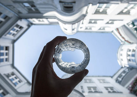 Someone holding a glass ball in front of a building