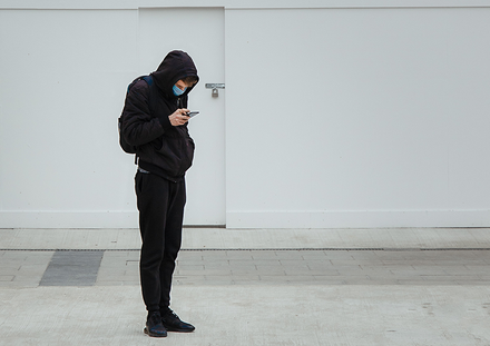 Man with face mask looking at his smartphone