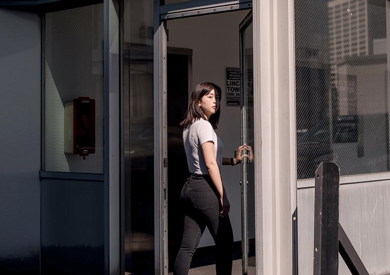 Woman is entering a building through a glass door
