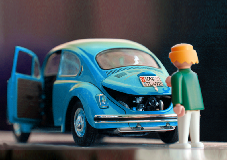 Orange hair Lego toy looking at a blue beetle car.