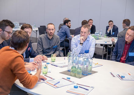 Business people sitting around table at Tapkey World 2019