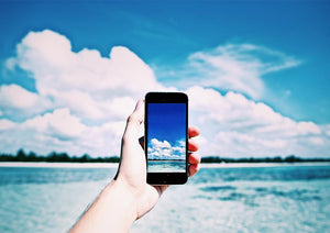 Person holding iPhone. Clouds in the background.