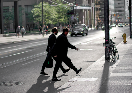 Two businessmen crossing a road