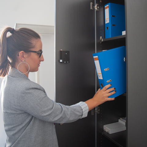 Woman taking out blue folder from a locker