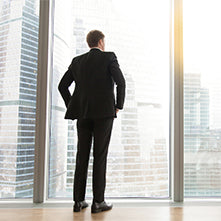Business man standing in front of a glass window