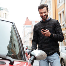 Smiling man standing next to a car with smartphone in his hand