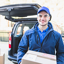 Delivery man with blue jacket holding a package