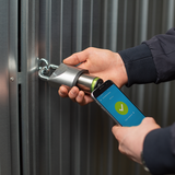 Someone holding a smartphone in front of a Tapkey Padlock.