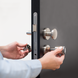Someone installs a Tapkey Smart Lock on a black door.