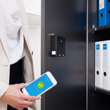 Woman opens a cabinet with a smartphone, where furniture lock is installed.