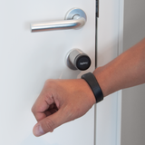 A hand with a NFC Wristband on it. In the background is a Tapkey Smart Lock.