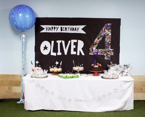 Modern boy's birthday dessert table backdrop with wrapping paper and chalkboard pens, with a jumbo marble balloon.