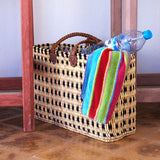 view of a large rectangular flat based Moroccan shopping basket handmade with woven palm fibres and long plaited leather handles