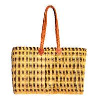 Front view of a large rectangular flat based Moroccan shopping basket handmade with woven palm fibres and long plaited leather handles