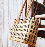 View of a medium sized, rectangular, flat based Moroccan shopping basket handmade with woven palm fibres and long plaited leather handles hanging on a chair