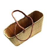 Top view of a large rectangular flat based Moroccan shopping basket handmade with woven palm fibres and long plaited leather handles