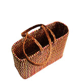 Top view of a medium sized, rectangular, flat based Moroccan shopping basket handmade with woven palm fibres and long plaited leather handles