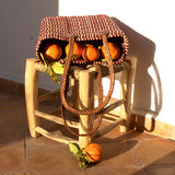 View of a small sized, rectangular, flat based Moroccan shopping basket handmade with woven palm fibres and long plaited leather handles on a stool with oranges