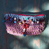 view of a multicoloured Moroccan clutch bag handmade using sabra silk embroidery threads with a shocking pink lining and zip closure
