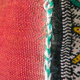 Close-up view of a multicoloured, handmade, geometrically patterned vintage Moroccan wool cushion