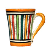 Front view of a medium sized ceramic Moroccan mug, multi-coloured stripes with orange rim and handle