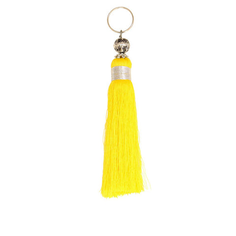 front view of a bright yellow Moroccan tassel handmade with embroidery silks and a metal bead