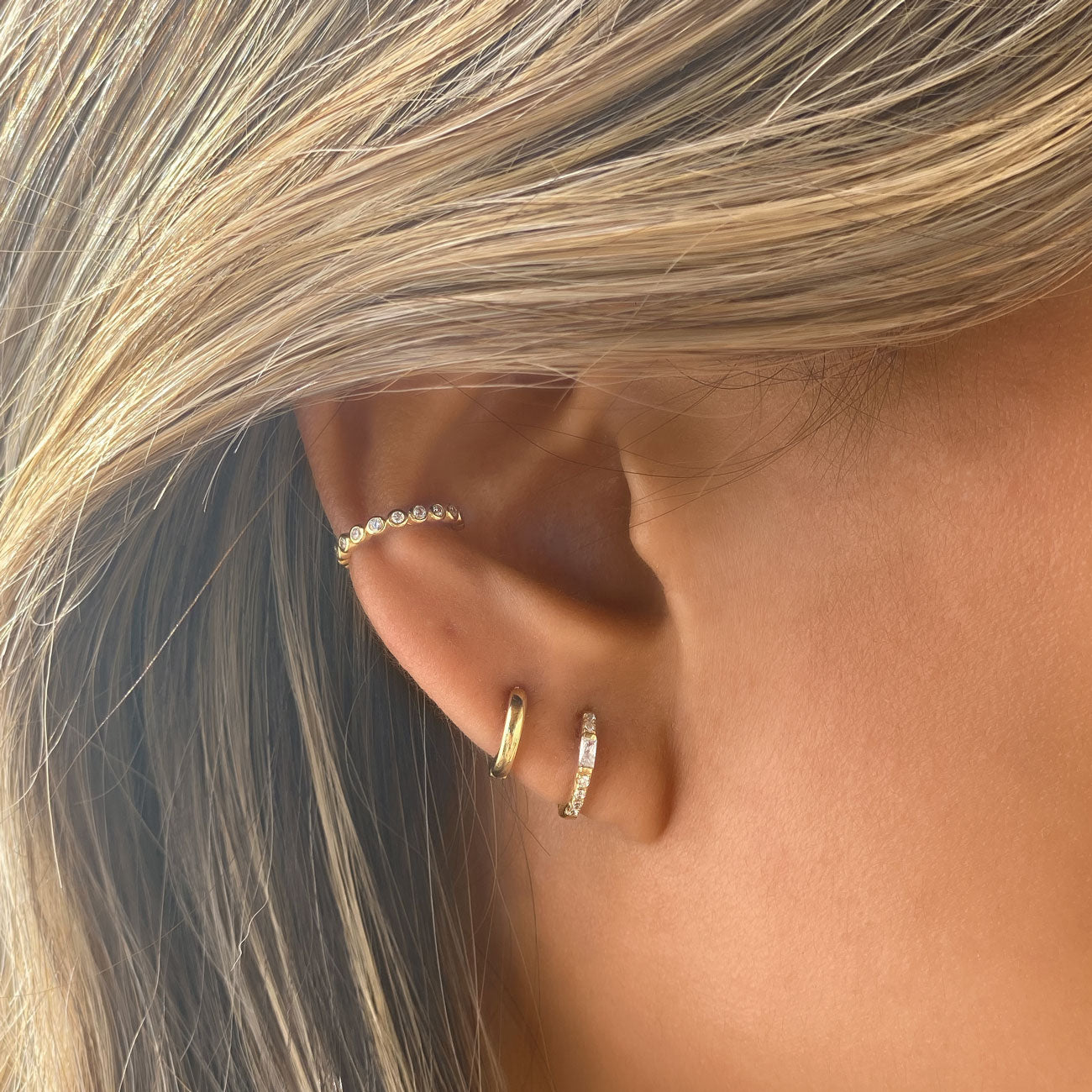 Gold huggie earrings paired with pave conch ear cuff