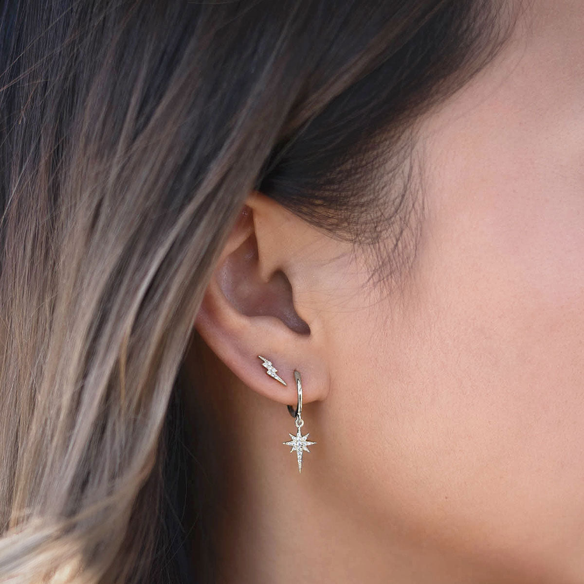Sterling Silver Starburst Huggie Earrings paired with tiny Lightning Bolt Studs