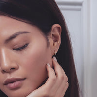 Model wearing rose gold tiny cross huggies with conch earring