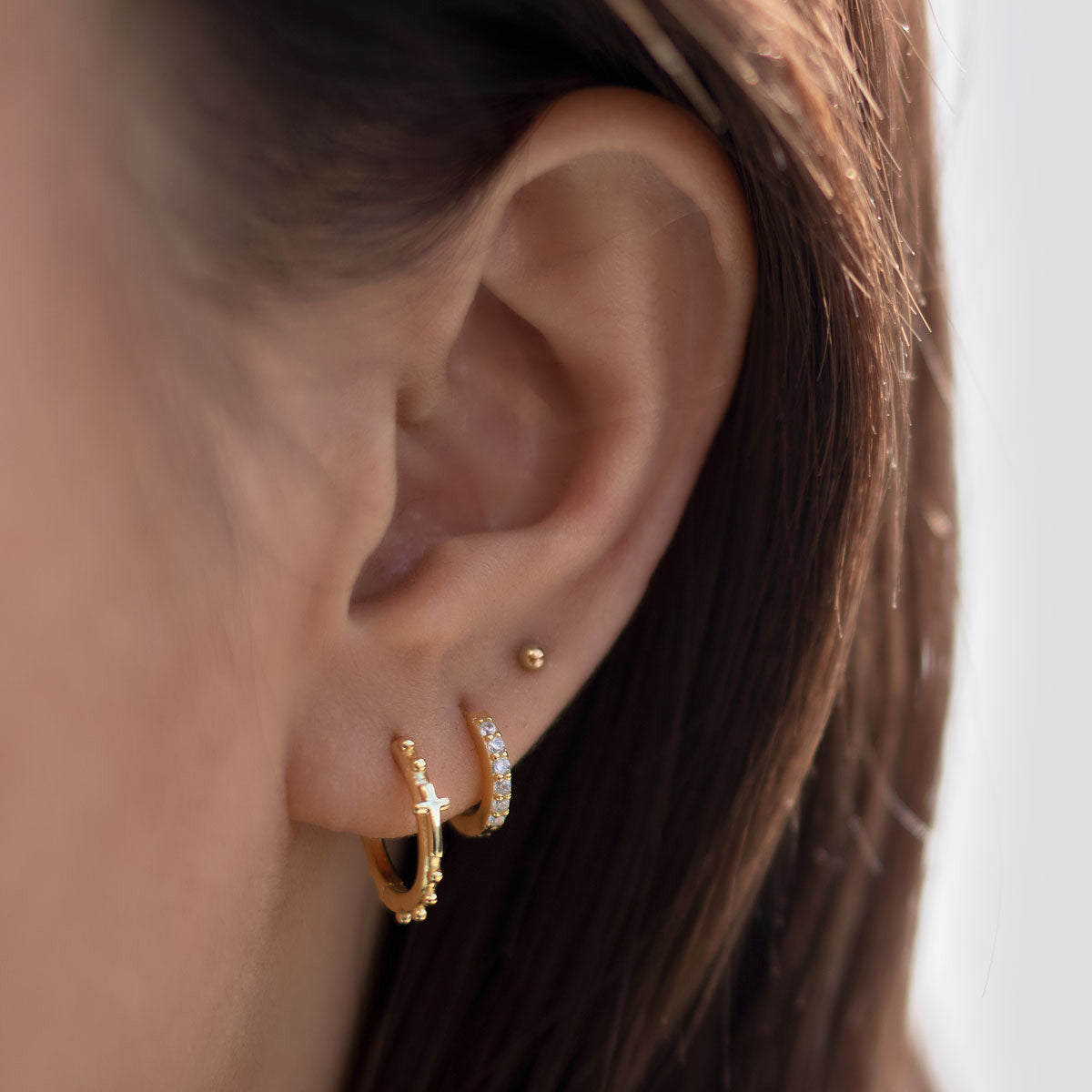 Ear stack made of Gold Cross Bead Huggies, Pave Gold Huggie, and Tiny Sphere stud earring
