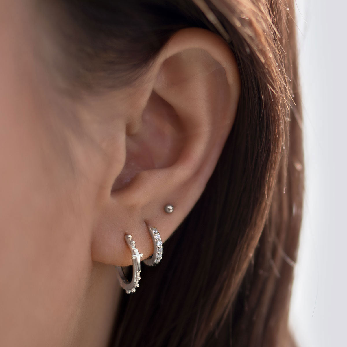 Ear Stack made up of Silver Cross Huggies, Pave Huggie Earrings and Tiny sphere stud earring