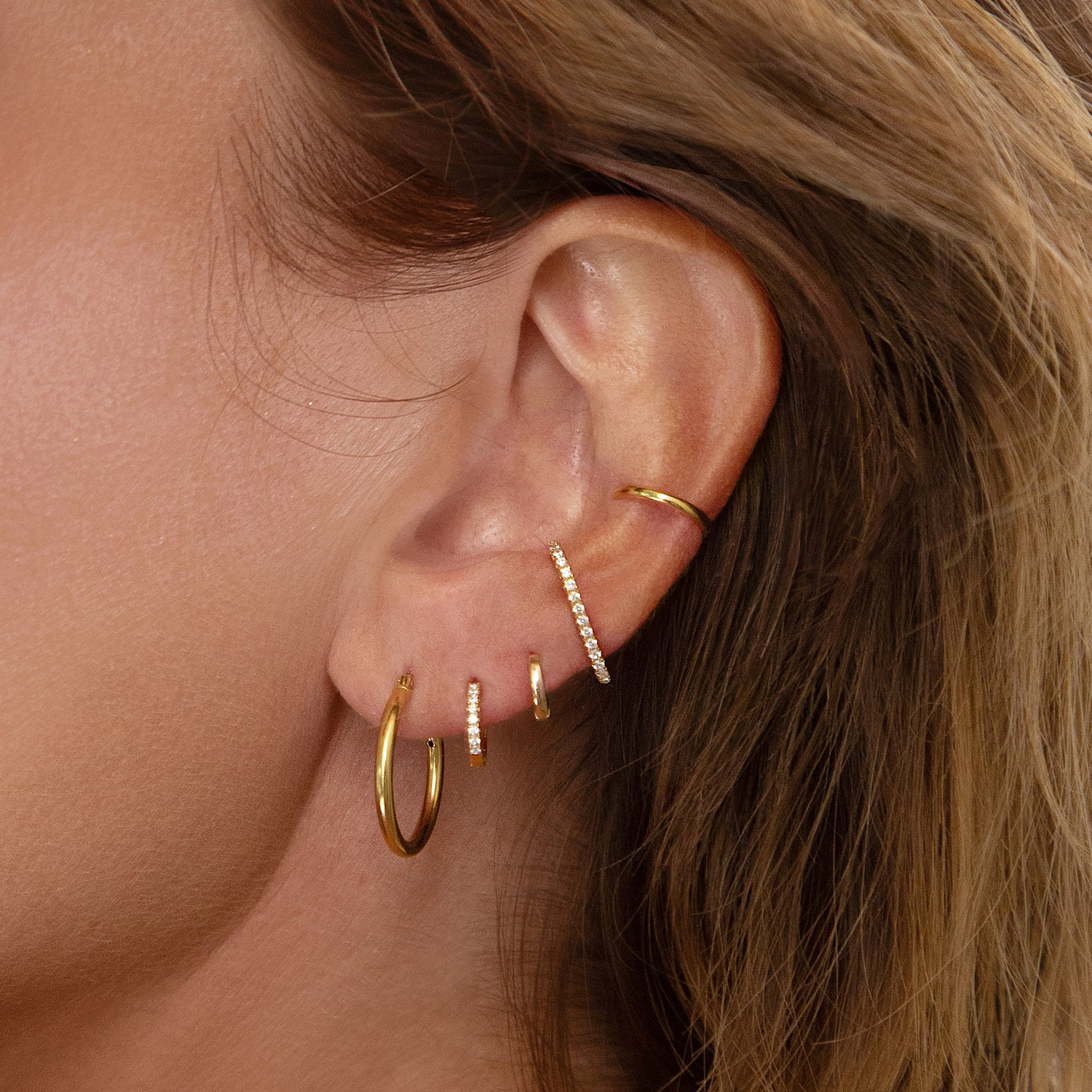 Gold ear stack made of hoops, huggie earrings, suspender earrings and ear cuff