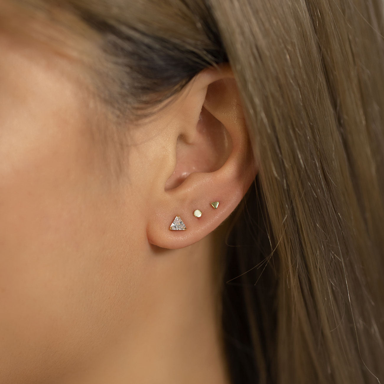 Tiny Gold circle and triangle studs on second and third piercing with Triangle CZ Stud Earring
