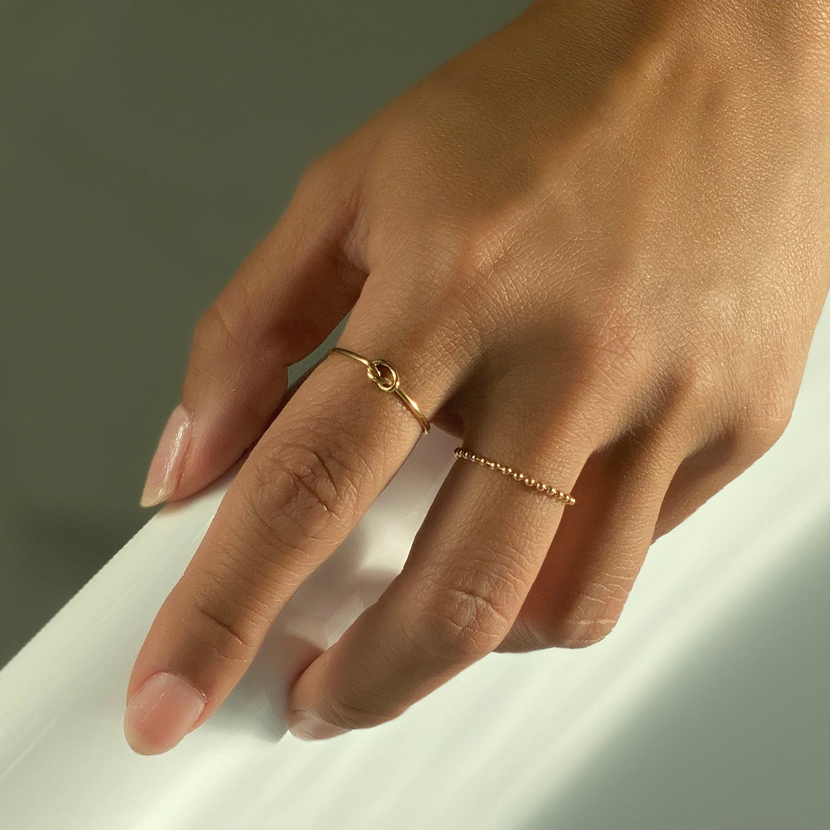 Hand wearing dainty gold knot ring and bead chain ring