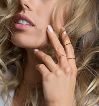 Dainty gold stackable rings on fingers