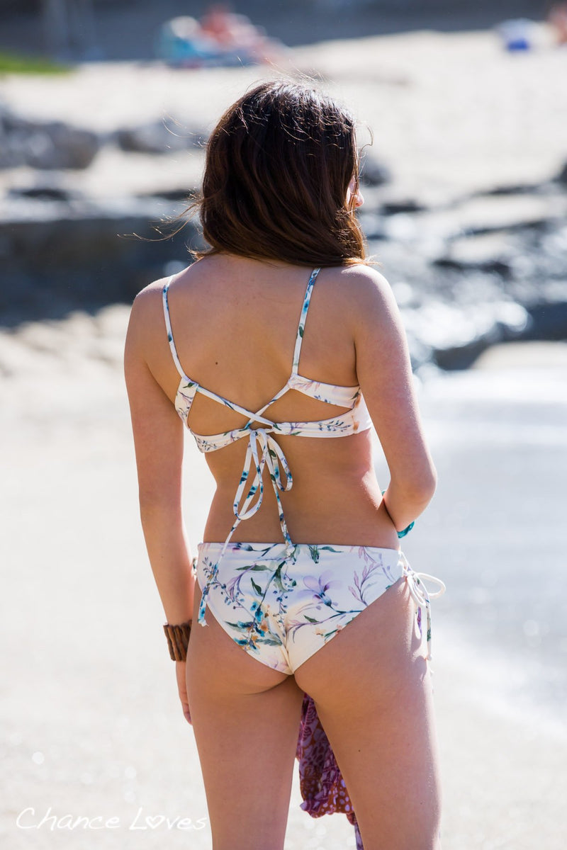 A girl on the beach is showing the backside of Floral Bikini Bottoms and Top, with adjustable ties.